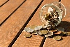 Diverse muntstukken zijn verspreid op een houten lijst Het concept armoede stock afbeeldingen