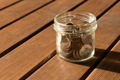 Diverse muntstukken zijn verspreid op een houten lijst Het concept armoede stock foto's