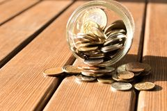Diverse muntstukken zijn verspreid op een houten lijst Het concept armoede royalty-vrije stock afbeeldingen