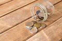 Diverse muntstukken zijn verspreid op een houten lijst Het concept po stock fotografie