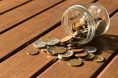Diverse muntstukken zijn verspreid op een houten lijst Het concept po stock foto's