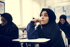 Diverse muslim children studying in classroom stock photography