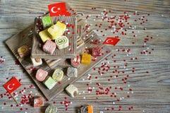 diverse nationale Oosterse snoepjes, met document vlaggen van Turkije, Turkse verrukking op een houten wit geborstelde tribune en stock fotografie