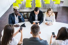 Diverse office people working on mobile phones. Corporate employees holding smartphones at meeting. serious multiracial. Diverse office people working on mobile royalty free stock photos