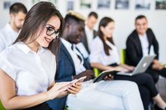 Diverse office people working on mobile phones, corporate employees holding smartphones at meeting. Serious multiracial royalty free stock photo