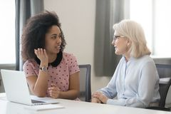 Diverse old and young female colleagues talking at work