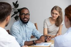 Diverse people discussing project sitting together around the of. Diverse multinational young professional millennial company members gathered together in office royalty free stock photo