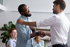 Company boss congratulating handshaking with successful employee. Diverse people gathered in meeting executive manager shake hands with black employee impressed stock photo