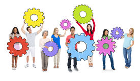 Diverse People Holding Colorful Cogs.  Stock Photo