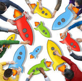 Diverse People Holding Colorful Rocketships Stock Photos