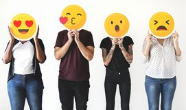Diverse people holding emoticon icons Stock Images