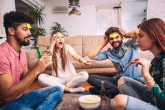 Diverse people playing game guess who and having fun. At home Stock Image