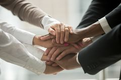 Diverse people putting hands together promising help and support. Diverse people putting stacked hands together promising help and support starting common Royalty Free Stock Images