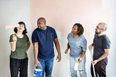 Diverse people renovating the house stock photography