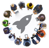 Diverse People Using Devices with Rocket Symbol. Diverse People Using Digital Devices with Rocket Symbol Stock Photos