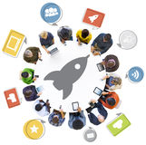 Diverse People Using Devices with Rocket Symbol. Diverse People Using Digital Devices with Rocket Symbol Royalty Free Stock Image