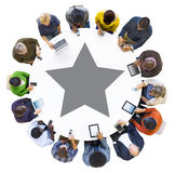 Diverse People Using Devices with Star Symbol. Diverse People Using Digital Devices with Star Symbol Around the Table Stock Photography