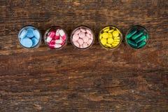 Diverse pillen en capsules in glascontainers Stock Foto