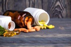 Diverse pillen en containers met groene bladeren Stock Fotografie