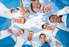 Diverse professional cleaners standing in huddle against sky. Directly below shot of diverse professional cleaners standing in huddle against sky Stock Photo