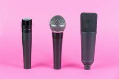 Diverse professionele microfoons op roze achtergrond Stock Afbeelding