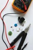 Diverse radiocomponenten, het hulpmiddel en het metende hulpmiddel op een witte achtergrond Stock Afbeeldingen