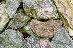 Diverse rotsen als achtergrond groot en klein voor metaalnetwerk stock foto's