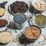 Diverse ruwe ongekookte korrels, bonen, graangewassen in kommen en koppen Stock Fotografie