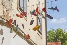 Diverse schoenen die van een kabel hangen stock afbeeldingen