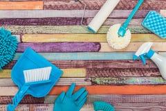 Diverse schoonmakende die hulpmiddelen op een kleurrijke lijst worden geplaatst stock afbeeldingen