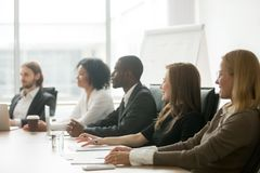 Diverse smiling businesspeople sitting at conference table at gr. Diverse smiling business people sitting at conference table at group meeting or corporate royalty free stock image