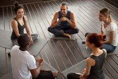 Diverse smiling people sitting on mats talking before yoga train. Diverse smiling people sitting on mats in circle relaxing talking before yoga training, happy Royalty Free Stock Photos