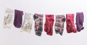 Diverse sokken die op een draad hangen stock afbeeldingen