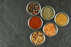 Diverse soorten kruiden in glaskommen op een leiachtergrond Voorbereiding voor het koken van kruidig voedsel Kruiden voor hoofdko Stock Afbeelding