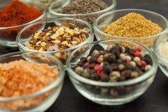 Diverse soorten kruiden in glaskommen op een leiachtergrond Voorbereiding voor het koken van kruidig voedsel Kruiden voor hoofdko Stock Afbeeldingen