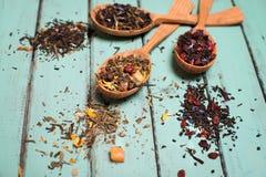 Diverse soorten thee in houten lepels op sjofel elegant hout backgr Royalty-vrije Stock Afbeeldingen