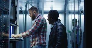 Diverse IT specialisten die mijnbouwlandbouwbedrijf in serverruimte plaatsen stock videobeelden