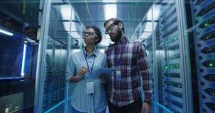 Diverse IT specialisten met tablet in serverruimte stock footage