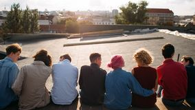 Diverse students rooftop unity communication. Group of diverse young students sitting on the roof top. Unity teamwork leisure communication Royalty Free Stock Images