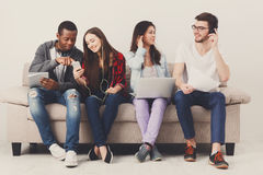 Diverse students using gadgets, sit on sofa Stock Photo