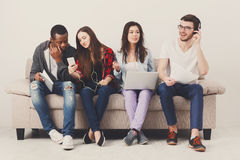 Diverse students using gadgets, sit on sofa Royalty Free Stock Photography
