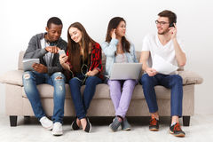 Diverse students using gadgets, sit on sofa Royalty Free Stock Image