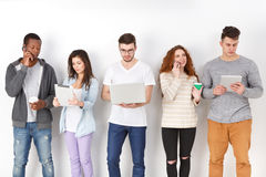 Diverse students using gadgets, standing in line. Modern education. Diverse students using gadgets, standing in line on white studio background indoors, copy stock photo