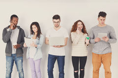 Diverse students using gadgets, standing in line Royalty Free Stock Photos