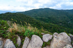 Diverse Taiwan landscape of huge rocks, tall grass, low hills, and forested mountains along the Jin Mian trail in Neihu Stock Photos
