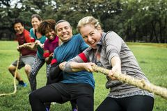 Diverse team competing in tug of war stock photo