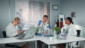 Diverse team of research scientists observing collegue's experiment with liquid in conical flask. stock footage