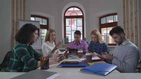 Diverse team using application on mobile phone. Young business team using gadgets in the creative office. Coworkers holding modern device in the boardroom stock footage