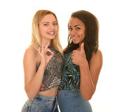 Diverse teen girls. Diverse pair of teen girls dressed in blue jeans and halter tops embracing with thumbs up and okay signs Royalty Free Stock Image