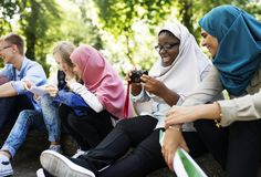 A diverse teenager group hang out in the park stock photo